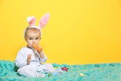 Cute little baby in bunny ears sitting on plaid. On color background Royalty Free Stock Photography