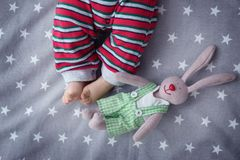 Cute little baby with bunny toy lying in cradle. At home Royalty Free Stock Photo