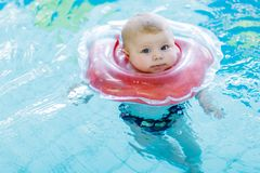 Cute little baby child learning to swim with swimming ring in an indoor pool Royalty Free Stock Photos