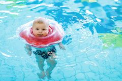 Cute little baby child learning to swim with swimming ring in an indoor pool Royalty Free Stock Photography