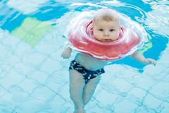 Cute little baby child learning to swim with swimming ring in an indoor pool Stock Image