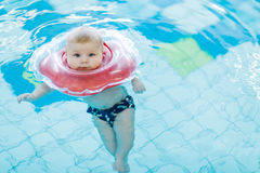 Cute little baby child learning to swim with swimming ring in an indoor pool Stock Photo
