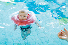 Cute little baby child learning to swim with swimming ring in an indoor pool Royalty Free Stock Image
