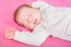 Cute little baby with closed eyes wearing knitted white clothes. Lying on pink plaid. 2 week old baby sleeping on pink sofa. Security and childcare concept royalty free stock photos