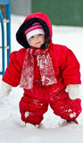Cute little baby clothing in big jumpers in the snowy park. Cute little baby clothing in big jumpers in the snowy winter park Royalty Free Stock Photography