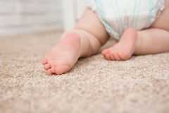 Cute little baby crawling on carpet indoors. Closeup stock photography