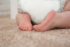 Cute little baby crawling on carpet indoors. Closeup stock photo
