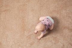 Cute little baby crawling on carpet indoors. Top view with space for text stock photos