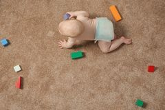 Cute little baby crawling on carpet with toys, top view royalty free stock photos