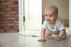 Cute little baby crawling on floor indoors. Space for text royalty free stock photo
