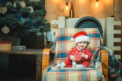 Cute little baby is decorating the Christmas tree indoors. Christmas winter holiday concept. Happy child with christmas royalty free stock images