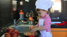 Cute little baby dressed as a cook helps mum in the kitchen stock footage