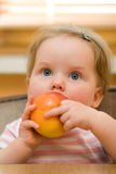 Cute little baby eating an apple Royalty Free Stock Photo