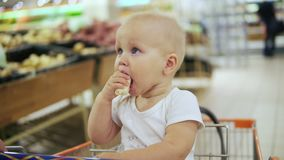 Cute little baby is eating banana and sitting in a shopping cart, while her mother is pushing the cart forward walking stock video