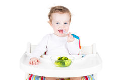 Cute little baby eating broccoli Royalty Free Stock Photography
