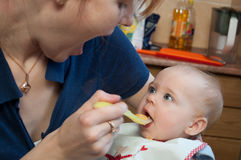 A cute little baby fed by her mother Royalty Free Stock Photos