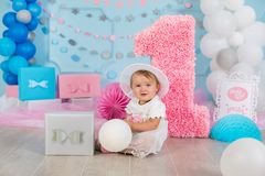 Cute little baby girl with big blue eyes wearing tutu hat and flower in her hair posing sitting in studio decorations with number. One celebrating her birthday stock photography