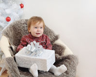 Cute little baby girl with big gift in hands near Christmas tree Stock Photo
