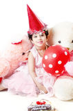 Cute little baby girl Celebrating her birthday. Surrounded with cake, Teddy bear doll,red balloons & hat  in white background Royalty Free Stock Photography