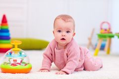 Cute little baby girl crawling on the carpet among the development toys Royalty Free Stock Photo