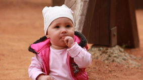 Cute little baby girl dressed in the pink clothing sitting on the playground in outdoor. stock video footage