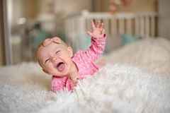 Cute little baby girl dressed in pink suit on the bed stock photography