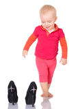 Cute little baby girl trying on her mother's shoes on white back Stock Image
