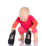 Cute little baby girl trying on her mother's shoes on white back Stock Photos