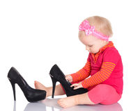 Cute little baby girl trying on her mother's shoes on white back Royalty Free Stock Photo