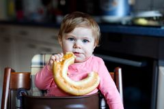 Cute little baby girl eating bread. Child eating for the first time piece of pretzel. Royalty Free Stock Photos