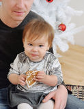Cute little baby girl eating cookies on father's knees near Chri Royalty Free Stock Image
