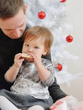 Cute little baby girl eating cookies on father's knees Stock Photos