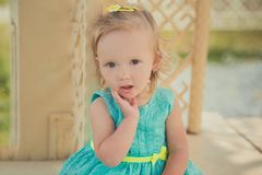 Cute little baby girl enjoying summer time in central park sights wearing colourful dress and sandals with blond hairs and pink ch. Eeks Stock Images