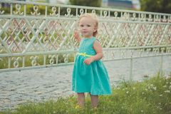 Cute little baby girl enjoying summer time in central park sights wearing colourful dress and sandals with blond hairs and pink ch. Eeks Royalty Free Stock Images