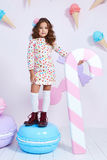 Cute little baby girl fashion pretty model dark blonde curly. Lady hair funny child birthday party fun children room candy bar sweet ice cream play with toy royalty free stock image