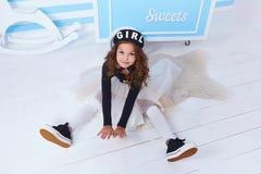 Cute little baby girl fashion pretty model dark blonde curly Stock Photo