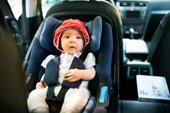 Little baby fastened with security belt in safety car seat. Cute little baby girl fastened with security belt in safety car seat stock image