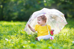 Cute little baby girl in the garden under an umbrella stock photos