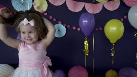 Cute little baby girl laughing and playing on her birthday party stock video