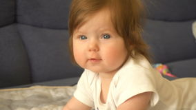 A cute little baby girl is looking into the camera stock video footage