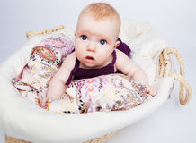 Cute little baby girl looks at. Cute little girl a baby lying in a wicker basket on her tummy and looks at the world looks big wet blue eyes Stock Photos