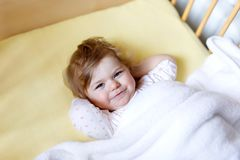 Cute little baby girl lying in cot before sleeping. Happy calm child in bed. Going sleep. Peaceful and smiling child. Looking on parents. Going to bed alone stock photo