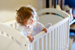 Cute little baby girl lying in cot after sleeping. Healthy happy child in bed climbing out. royalty free stock photo