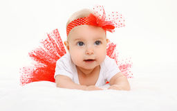 Cute little baby girl lying in red skirt on bed Stock Image