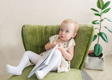 Cute little baby girl make funny face, holding book in hand. Kid sitting on armchair. Royalty Free Stock Image