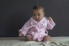 Baby girl on bed in bathrobe royalty free stock photography
