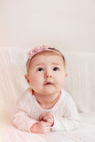 Cute little baby girl with pink flower headband looking up and e Stock Images