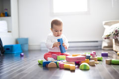 Cute little baby girl play with plastic bricks sitting indoors on a tiles floor Royalty Free Stock Image