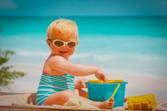 Cute little baby girl play with toys on beach. Vacation stock images