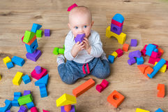 Cute little baby girl playing with colorful toy blocks. On the floor Royalty Free Stock Image